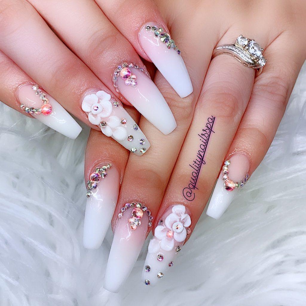 White/Pink Nail Polish with Rhinestones and White Flowers Nail Art.