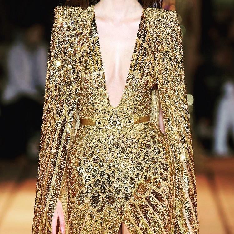 Detail of Deep V-Neck Gold Sparkling Long Gown with Padded Shoulder Cape.