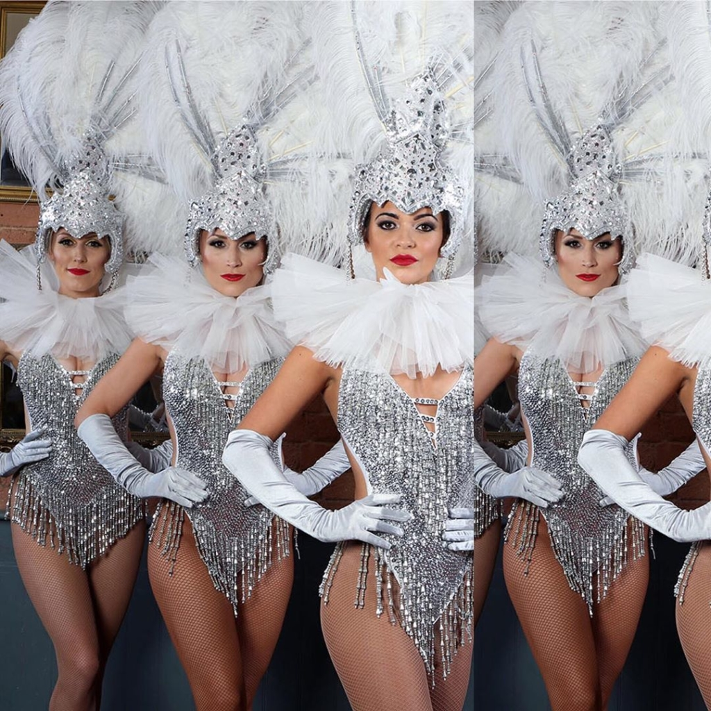 Silver Sequin Showgirl Leotard with Hanging Beaded Hemline and White Feather Head Dress.