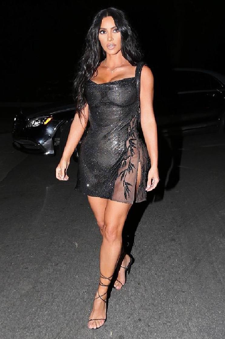 Celebrities Wearing Bling Kim Kardashian Revealing Her Assets Wearing a Black Mini Sequin-Embellished Strap Dress with Tie Up Heel Sandals
