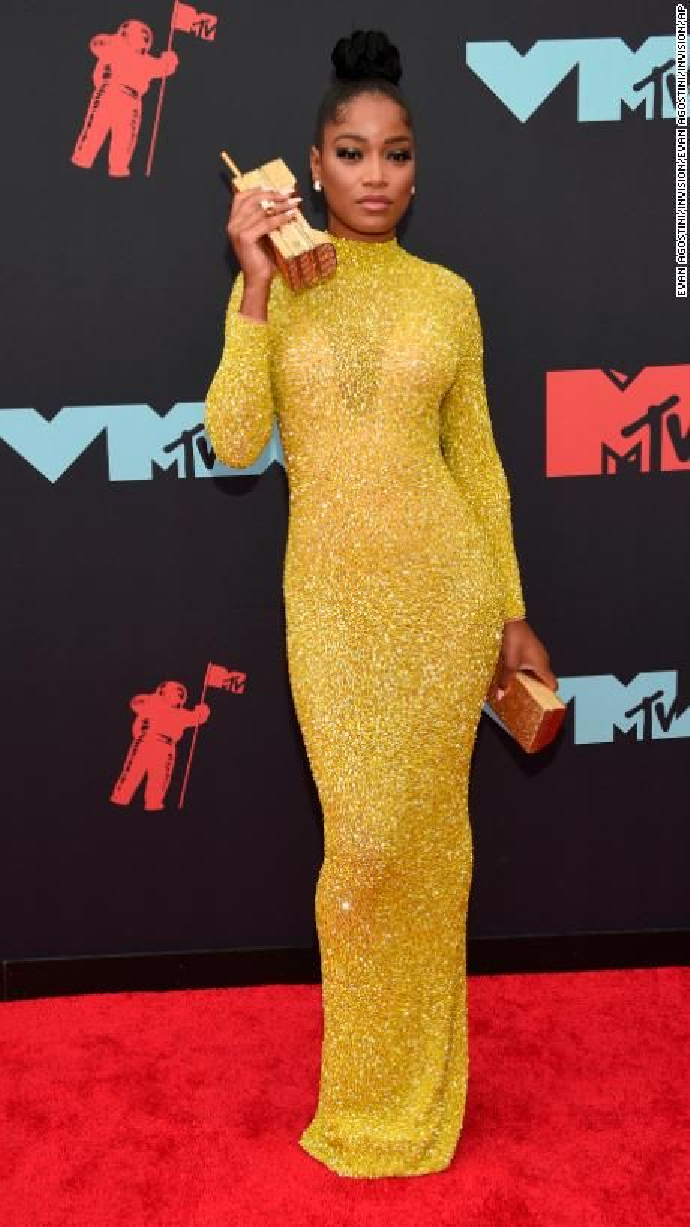 Celebrities Wearing Bling Palmer Evan Wears a Long Sleeves High Neck Sequin Gown with A Gold Phone Clutch