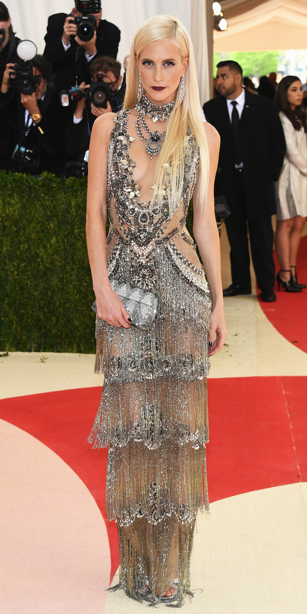 Celebrities Wearing Bling Poppy Delevingne Wears a Deep V-Neck Sleeveless Sequin and Embilleshed Gown with Silver Beaded Clutch