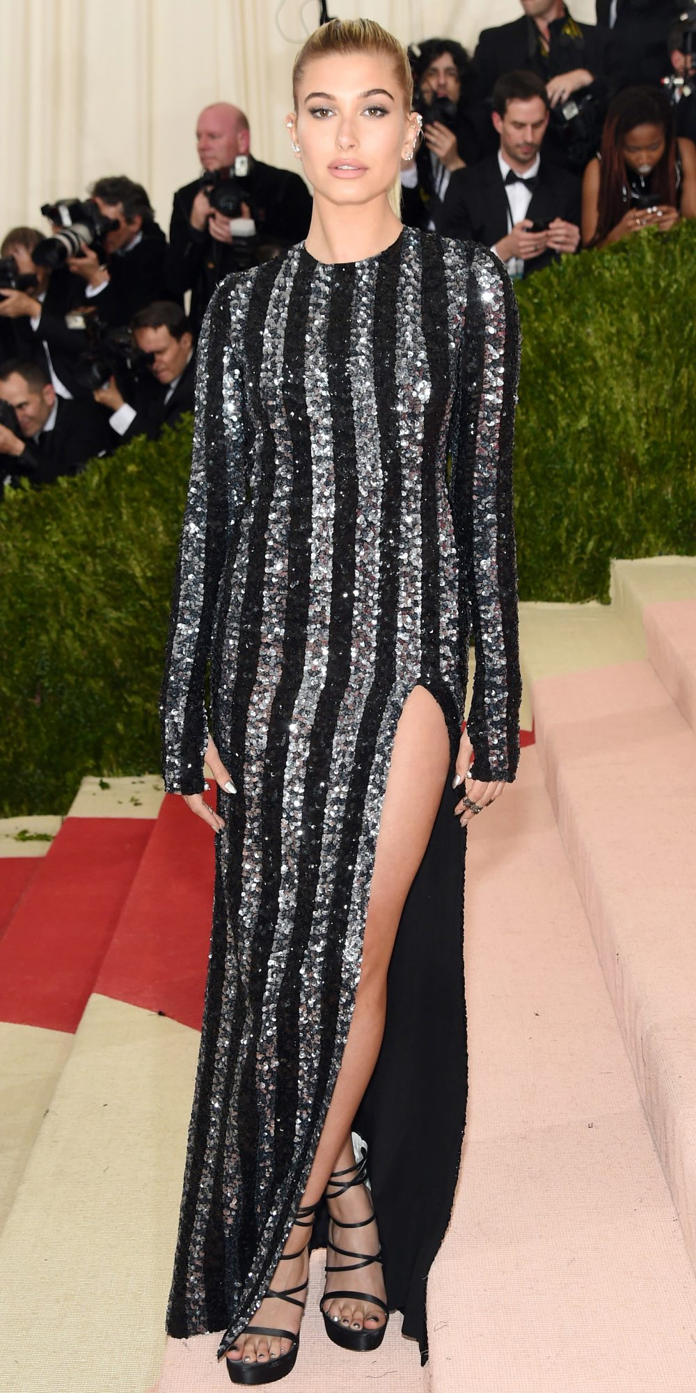 Celebrities Wearing Bling Hailey Baldwin Wears a Long Sleeves Black and Silver Stripes Sequin Gown with High Slit