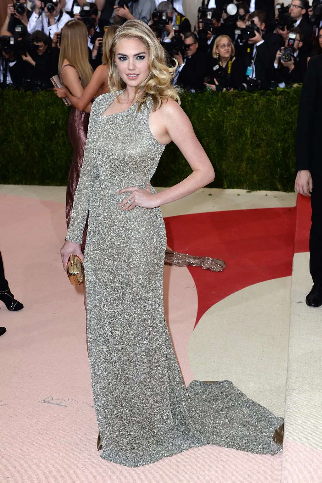 Kate Upton Wears Her One Side LOng Sleeves Sequin Gown with a Gold Clutch