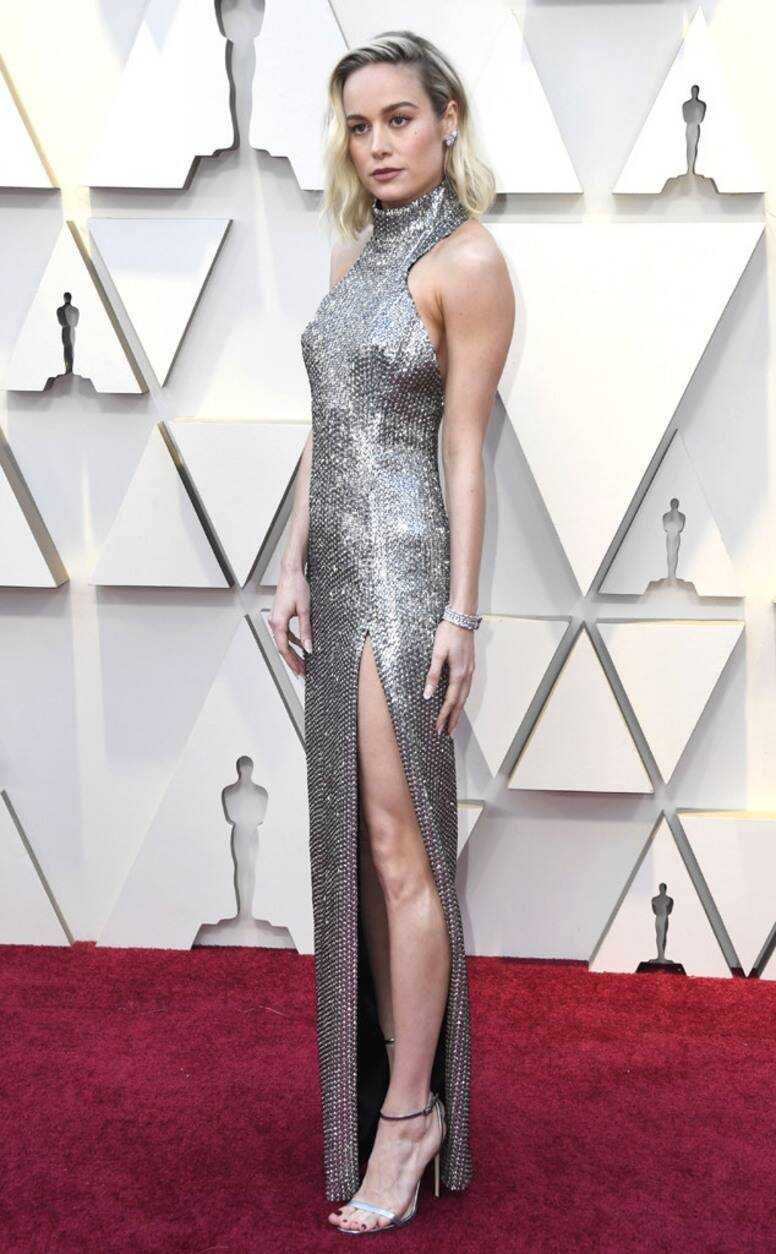 Red Carpet bling Brie Larson In A Long Silver Sequin Gown with A High Slit and Neckline with High Heels